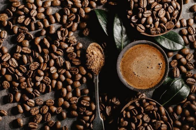top view of cup of brewed black coffee arranged with plenty of brown beans and green coffee leaves