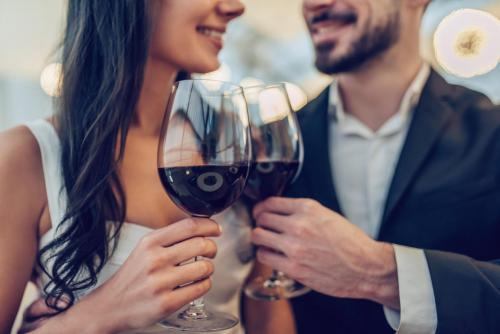 cropped image of loving couple is spending time together in modern restaurant attractive young woman in dress and handsom...