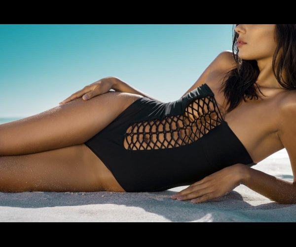 mid section of young woman in black swimsuit with stripes sunbathing on white sand fashion girl tanning on tropical beach...